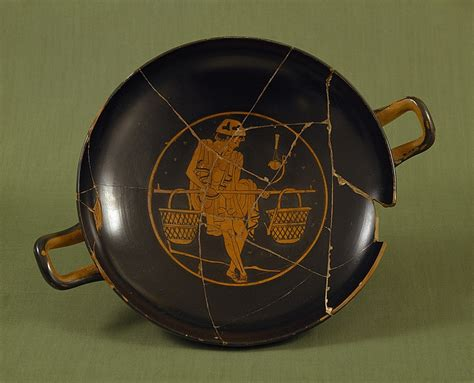 Kylix with a youth carrying pole with two baskets